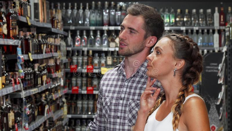 Couple discussing wine for sale at the supermarket. Handsome young men and his beautiful girlfriend choosing wine to buy at the supermarket. Lovely couple stock image
