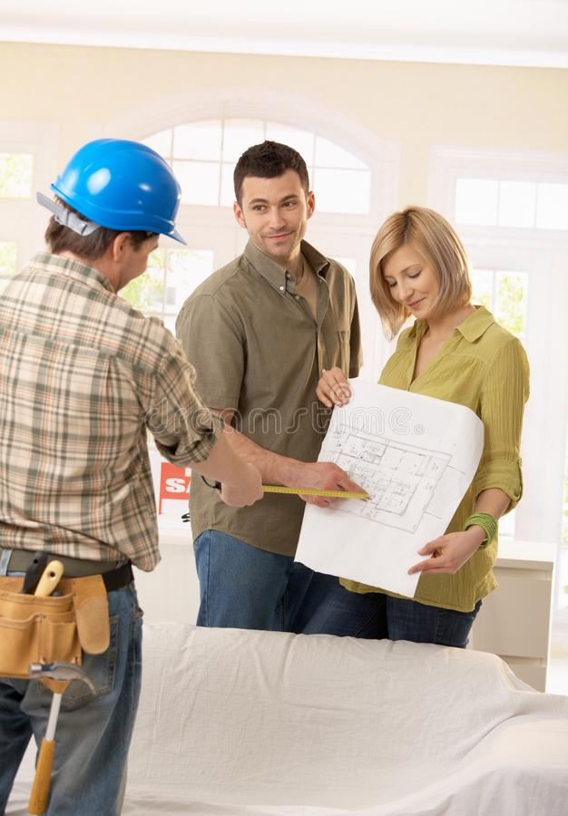 Couple in discussion with builder. Smiling couple discussing ground plan of new home with builder royalty free stock photo