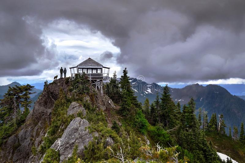 Couple with a dog standing on mountain top  by fire lookout hut under dramatic storm sky. royalty free stock photos