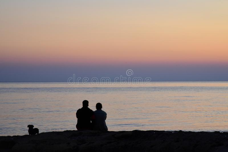 A couple with a dog watching the sunrise at the sea coast royalty free stock photos