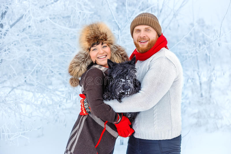 Couple with a dog in winter royalty free stock photo