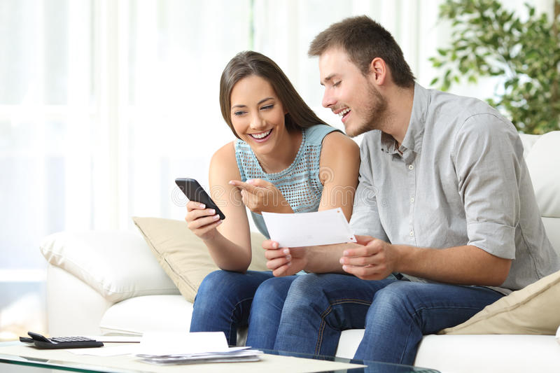 Couple doing accounting with a phone bank app. Couple doing accounting on line with a phone bank app sitting on a couch in the living room at home royalty free stock photography