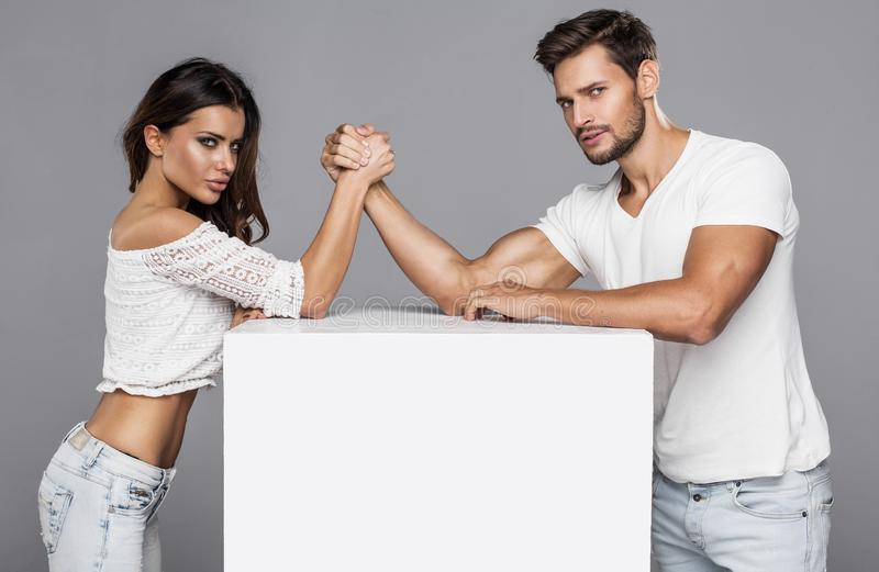 Couple doing arm wrestling challenge. Beautiful couple doing arm wrestling challenge isolated on gray royalty free stock photography