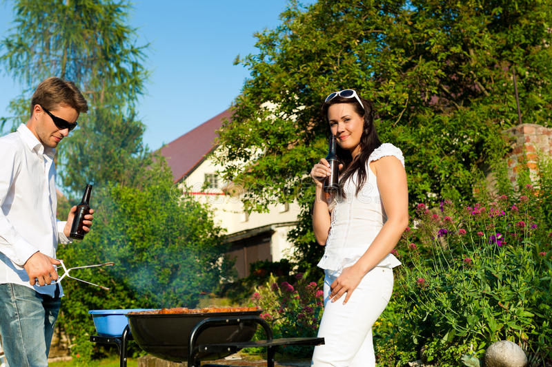 Couple doing BBQ in garden in summer