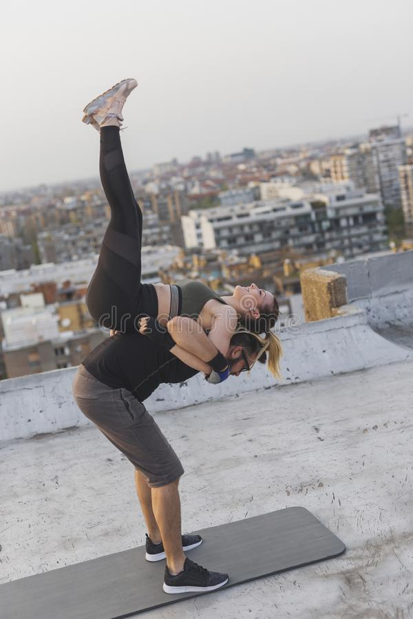 Couple doing candlestick exercise. Couple doing strength exercises on a building rooftop terrace, guy lifting a girl on his back while she is doing a candlestick stock images