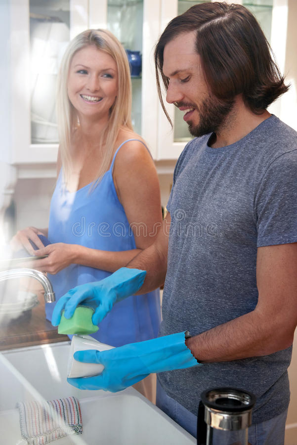 Couple doing the dishes. Happy caucasian couple doing household chores in the kitchen stock images