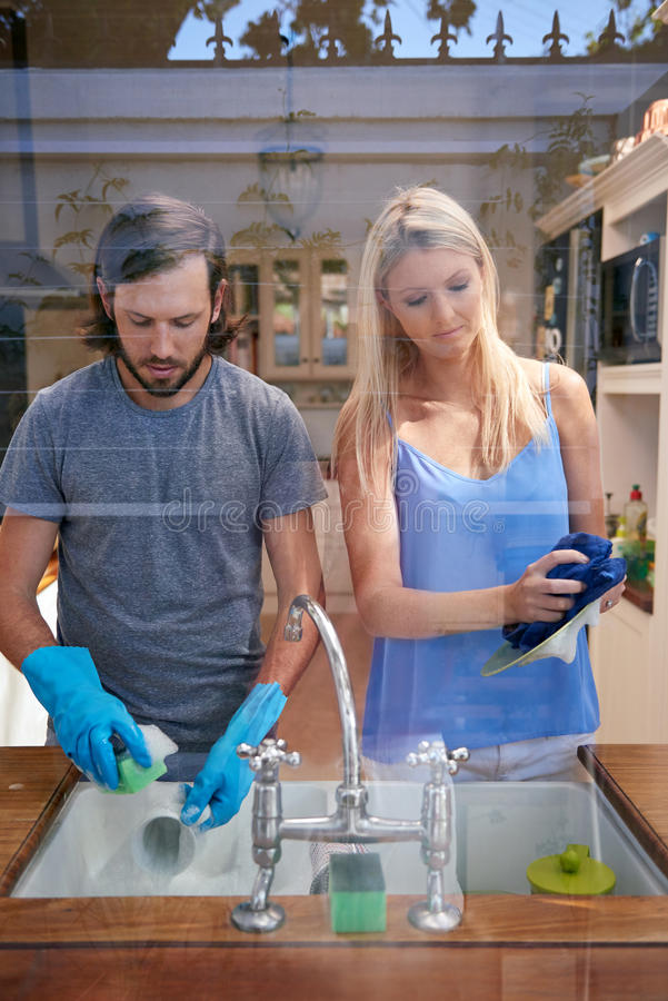 Couple doing the dishes. Young caucasian couple doing household chores in the kitchen image through window stock photos