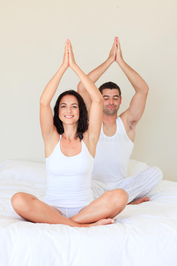 Couple doing exercises on bed. Young couple doing exercises on bed royalty free stock photos