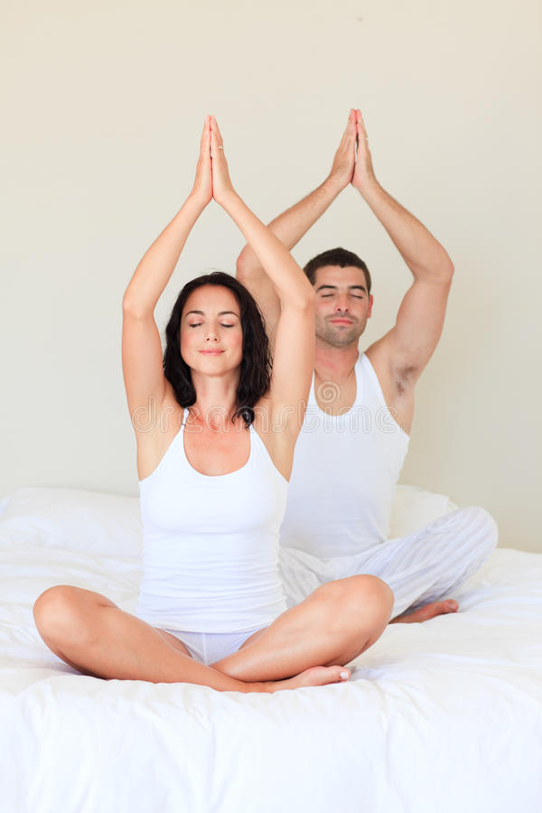 Couple doing exercises on bed with closed eyes. Young couple doing exercises on bed with closed eyes stock images