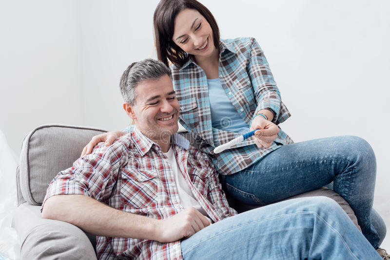 Couple doing a pregnancy test. Happy smiling couple at home doing a pregnancy test stock images