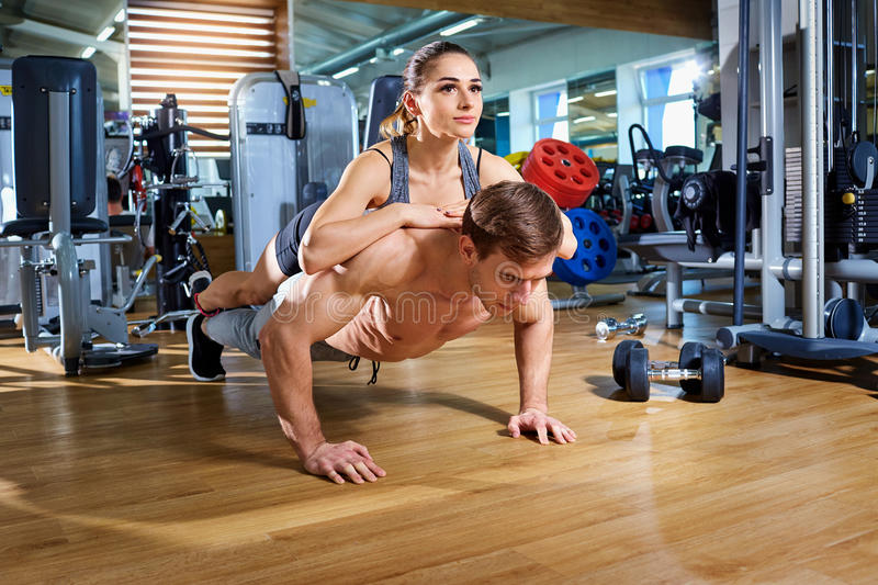 A couple doing push-ups on floor in the gym sport club.  stock photography