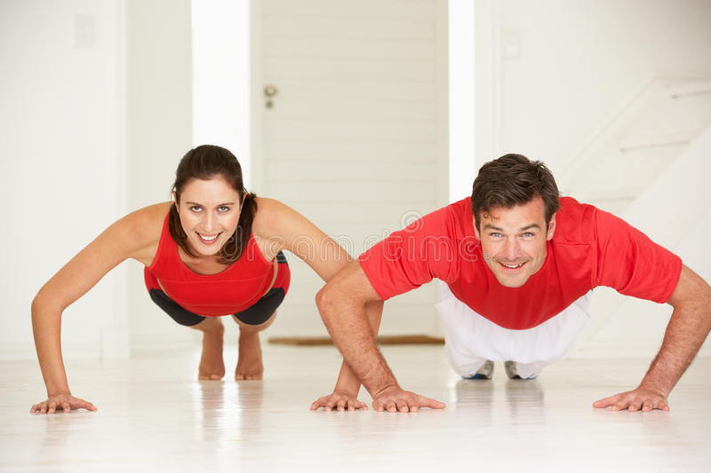 Couple doing push-ups in home gym royalty free stock photo