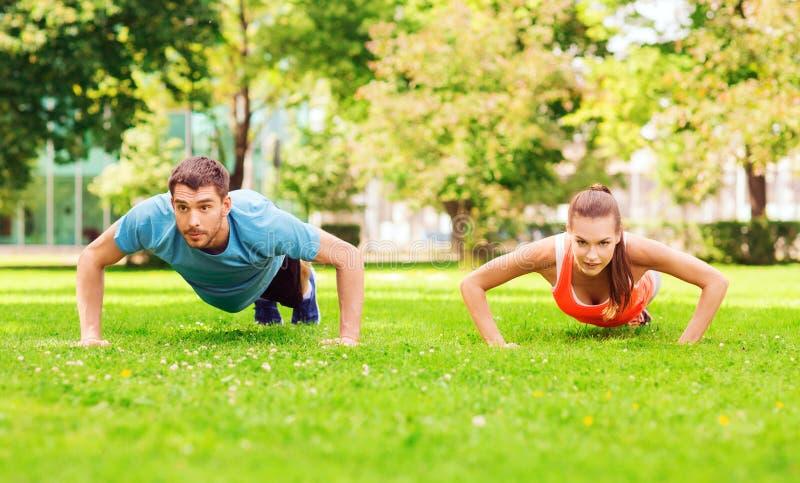 Couple doing push-ups outdoors royalty free stock photos