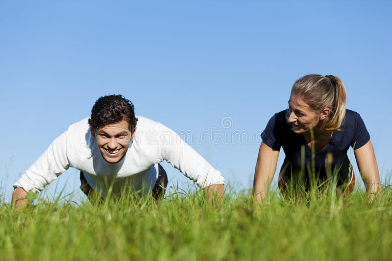 Couple doing push ups in summer grass. Couple - man and woman - doing push ups on a green meadow in summer, enjoying this exercise very much royalty free stock photography