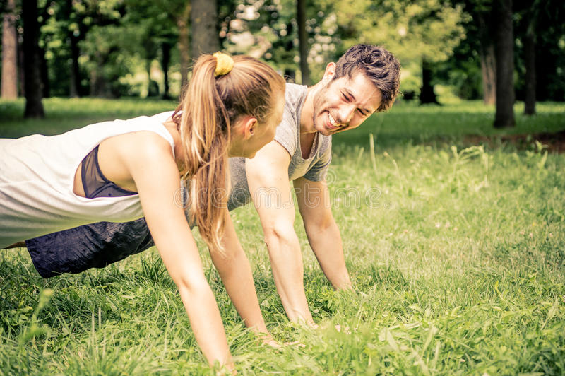 Couple doing push ups. Young couple doing push ups in a park - Two athletes training outdoors stock images