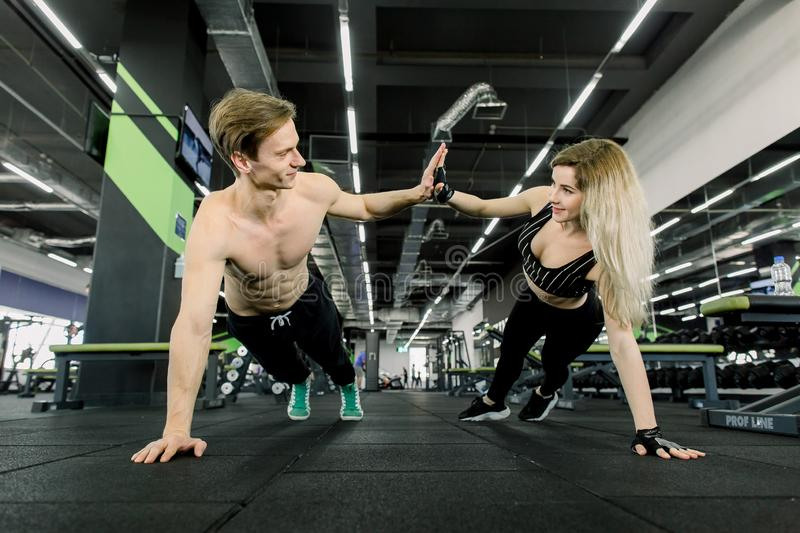 Couple doing pushups at training in gym. Young sporty couple working out together in a gym . Doing plank exercises while royalty free stock image