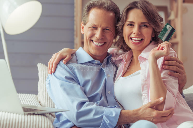 Couple doing shopping online. Happy beautiful couple is doing shopping online and smiling while sitting on sofa at home. Woman is holding a credit card stock photo