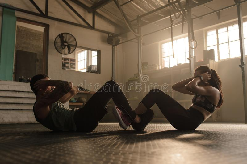 Couple doing sit-ups together in gym. People working out in gym. Fit men and women doing sit ups together royalty free stock photos