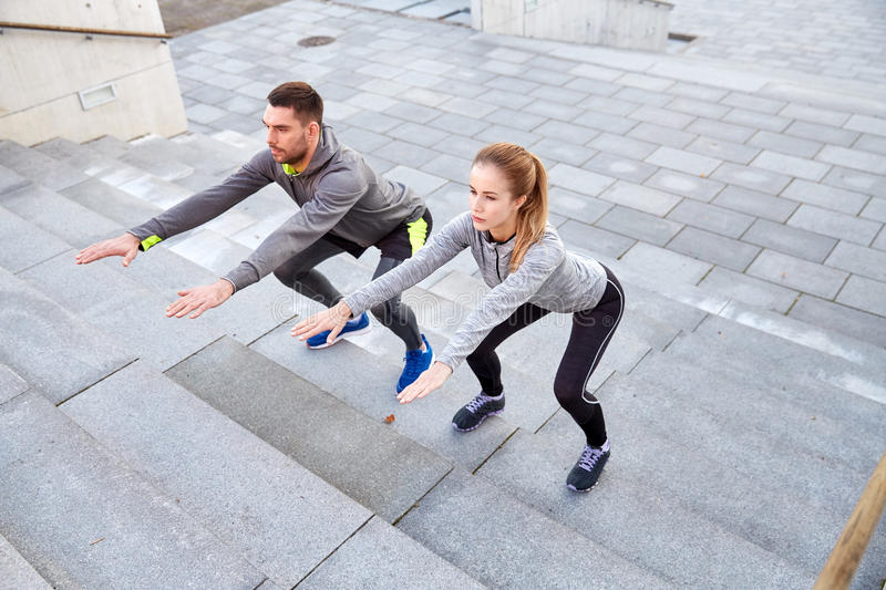 Couple doing squats on city street stairs. Fitness, sport, people, exercising and lifestyle concept - couple doing squats on city street stairs royalty free stock photos