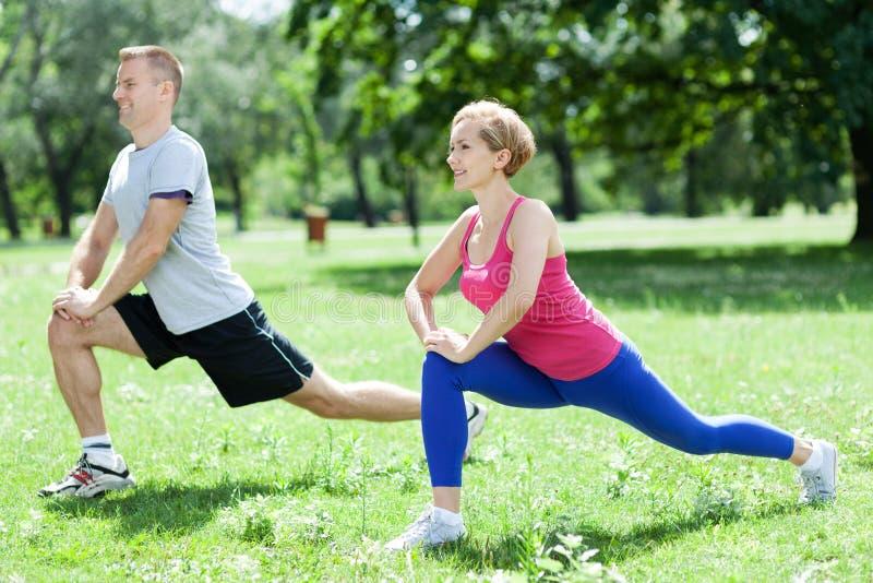 Couple doing stretching exercises royalty free stock photos