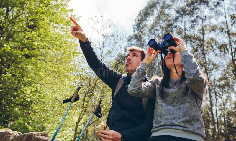 Couple doing trekking looking with binoculars royalty free stock images