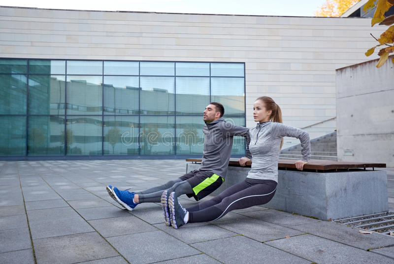 Couple doing triceps dip exercise outdoors. Fitness, sport, training, people and lifestyle concept - couple doing triceps dip exercise on bench outdoors stock photography