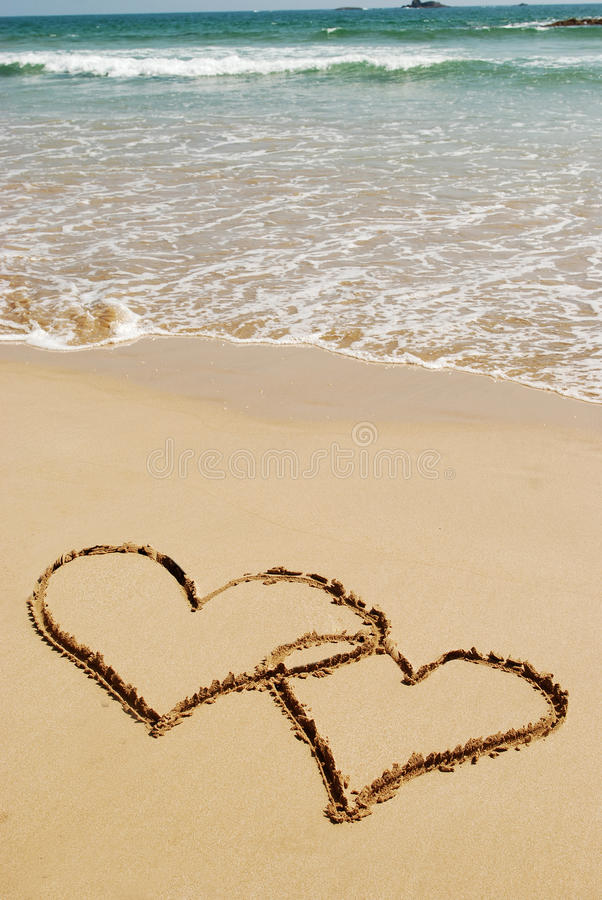 Couple drawing a heart on wet golden beach. Sand stock images