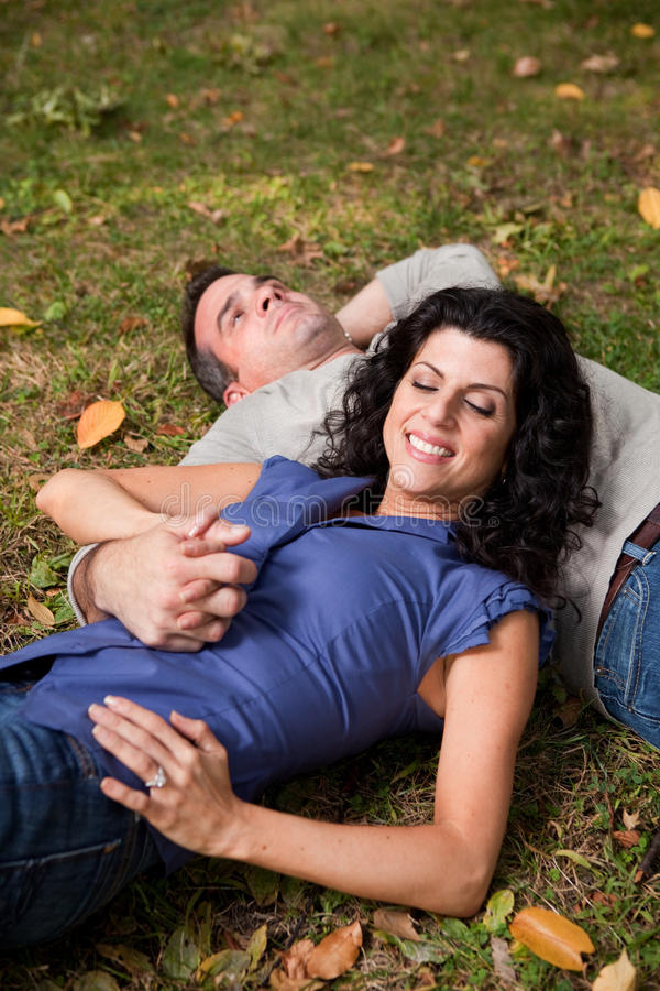 Couple Dream. A man and woman relaxing in the park laying in the grass and dreaming - focus on the woman royalty free stock photography