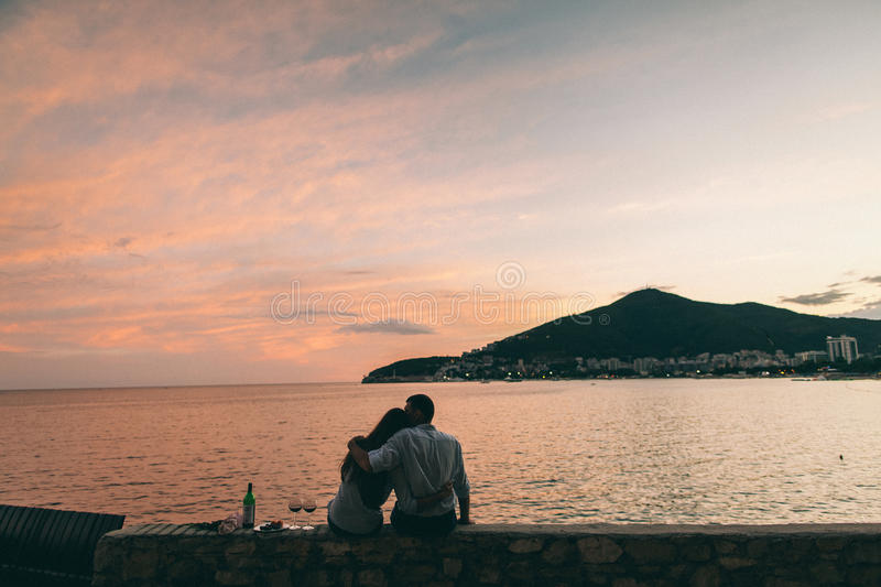 Couple drink wine at sunset beach. Montenegro royalty free stock images