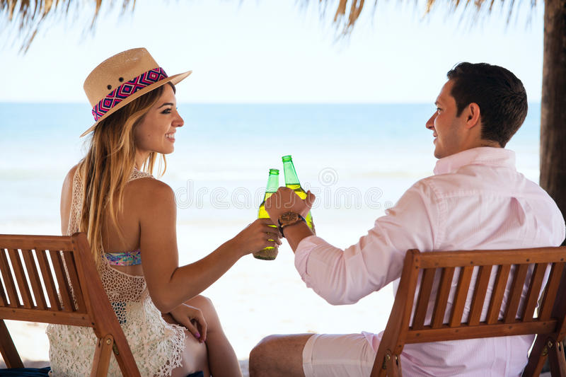 Couple drinking beer at the beach. Rear view of a young couple of newlyweds making a toast with some beer and enjoying their honeymoon at the beach stock images