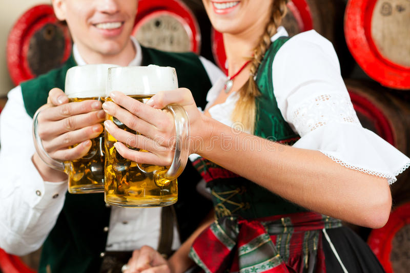 Couple drinking beer in brewery. Young couple, man and woman, in traditional Bavarian Tracht drinking beer in a brewery in front of beer barrels stock photography