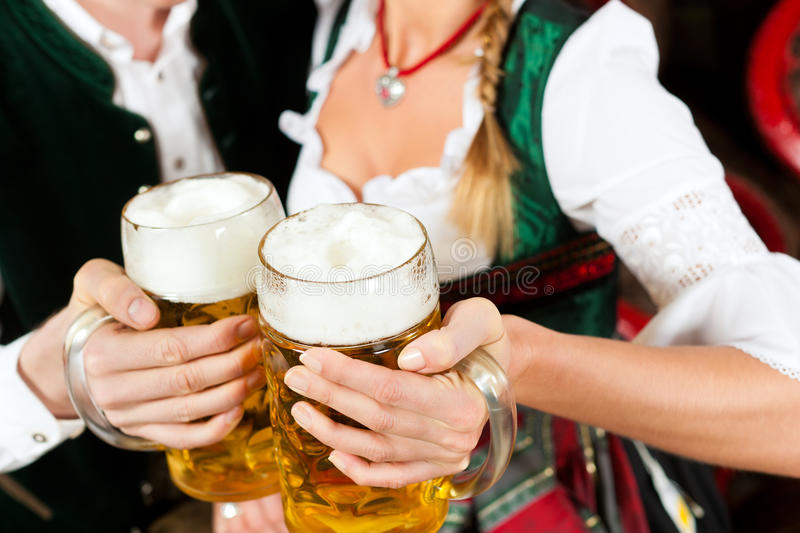 Couple drinking beer in brewery. Young couple, man and woman, in traditional Bavarian Tracht drinking beer in a brewery in front of beer barrels stock photos