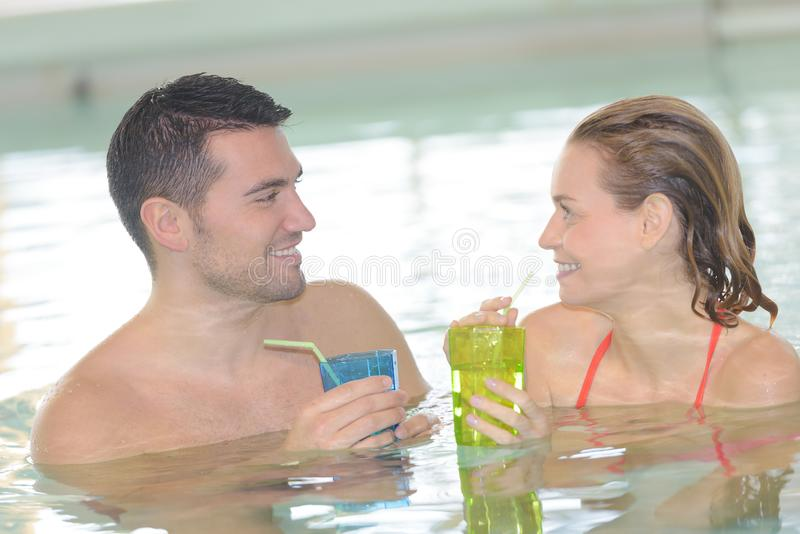 Couple drinking cocktail in swimming pool royalty free stock photo