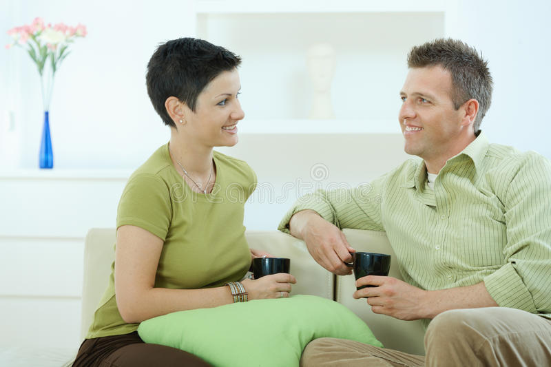 Couple drinking coffee. Young couple drinking coffee at home, sitting on couch, looking at each other, smiling royalty free stock image
