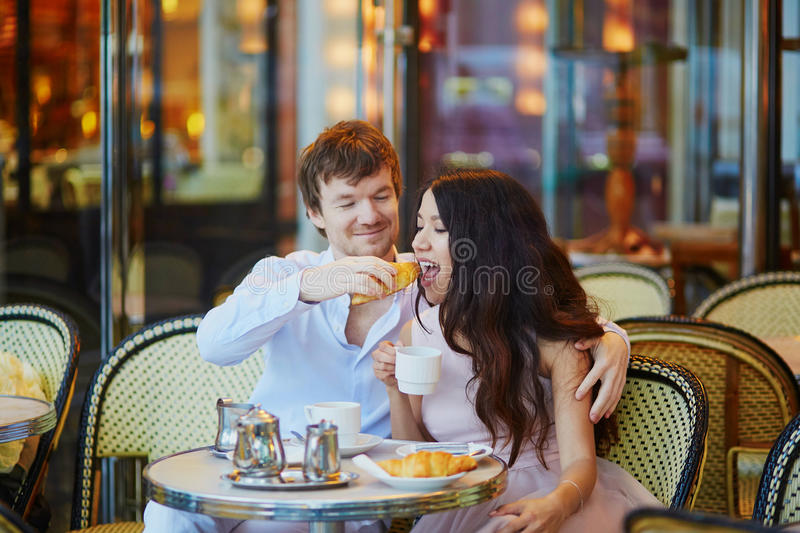 Couple Drinking Coffee And Eating Croissants In Parisian Cafe Stock