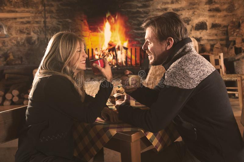 Couple drinking hot beverages in cafe in winter. Happy couple at the table drinking hot beverages in cafe with fireplace in winter. Woman and men in warm stock photo