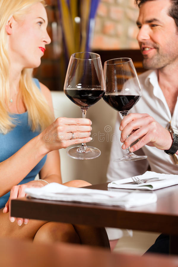 Couple drinking red wine in restaurant or bar. Attractive young couple drinking red wine in restaurant or bar, it might be the first date stock photo