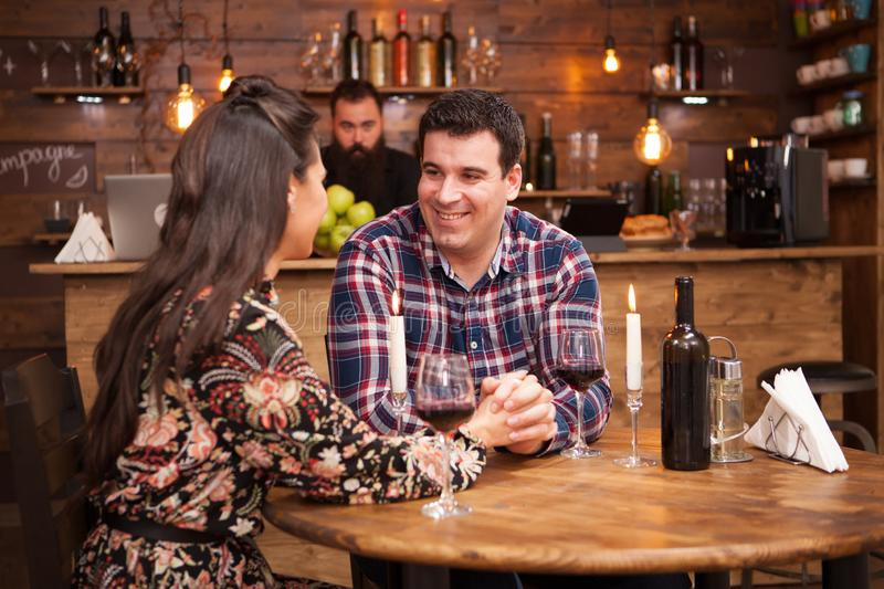 Couple drinking red wine and sharing a beautiful moment in a hipster pub. royalty free stock photos