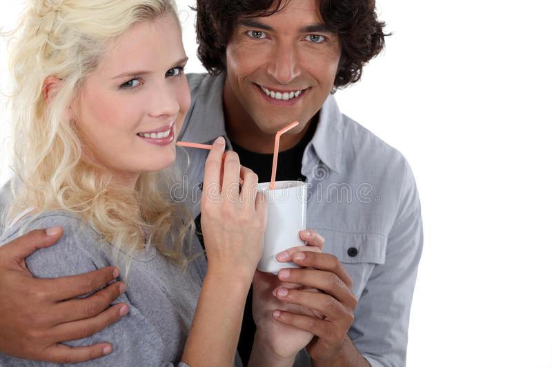 Couple drinking from same cup royalty free stock images