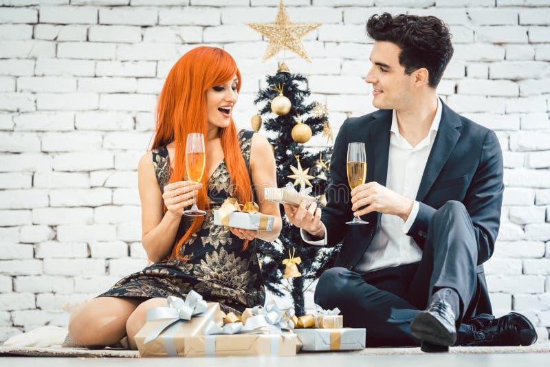 Couple drinking sparkling wine on Christmas stock photos