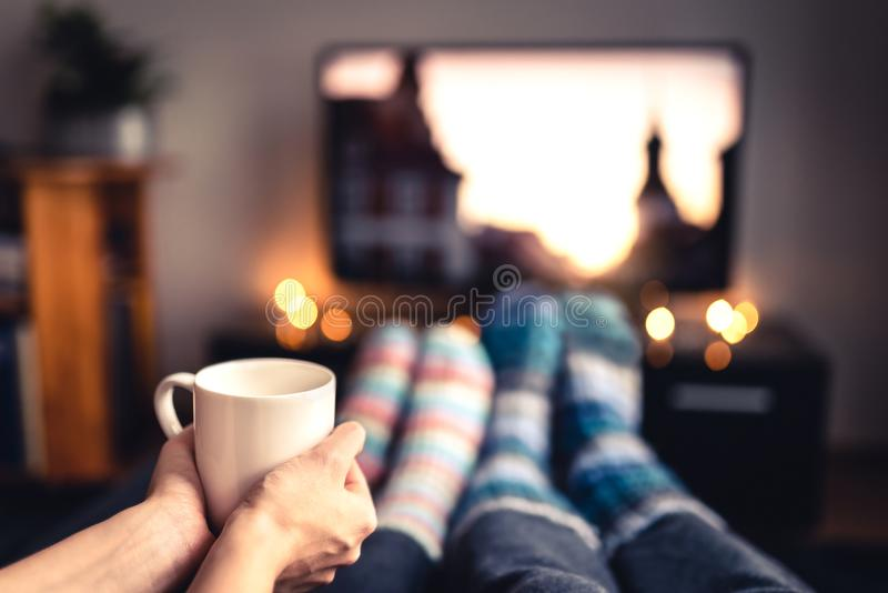 Couple drinking tea, hot chocolate, eggnog or mulled wine and watching tv in warm cozy woolen socks in winter. stock image