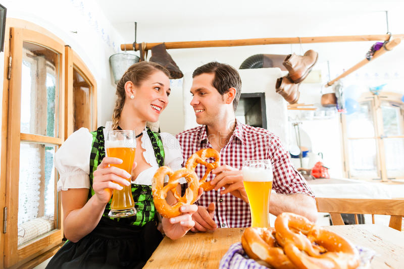 Couple drinking wheat beer in bavarian restaurant. Bavarian couple wearing traditional dress, flirting and drinking beer in restaurant royalty free stock image