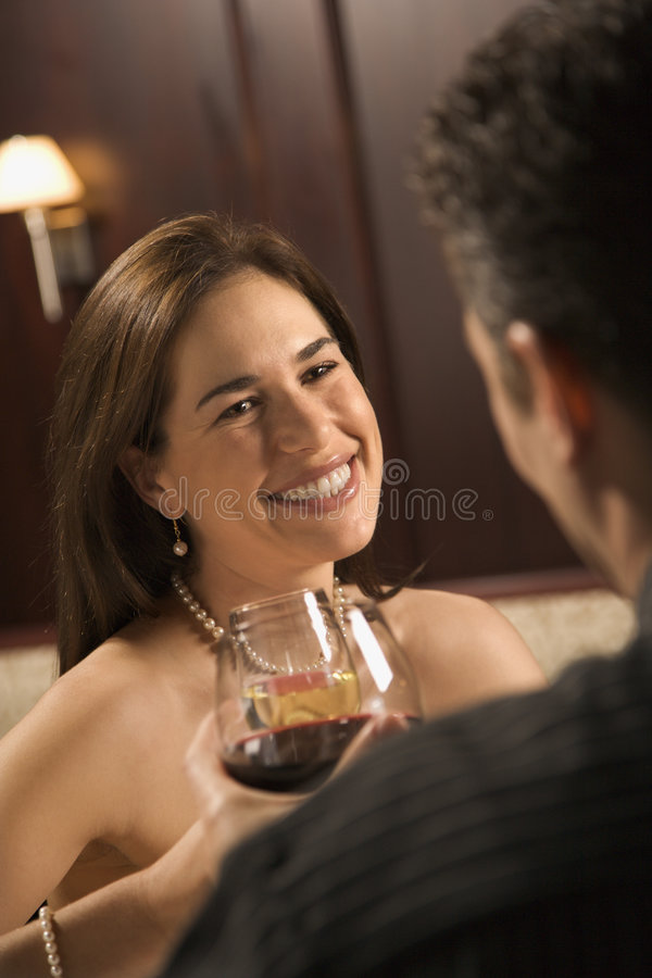 Couple drinking wine. Mid adult Caucasian couple holding wine glasses and smiling royalty free stock image