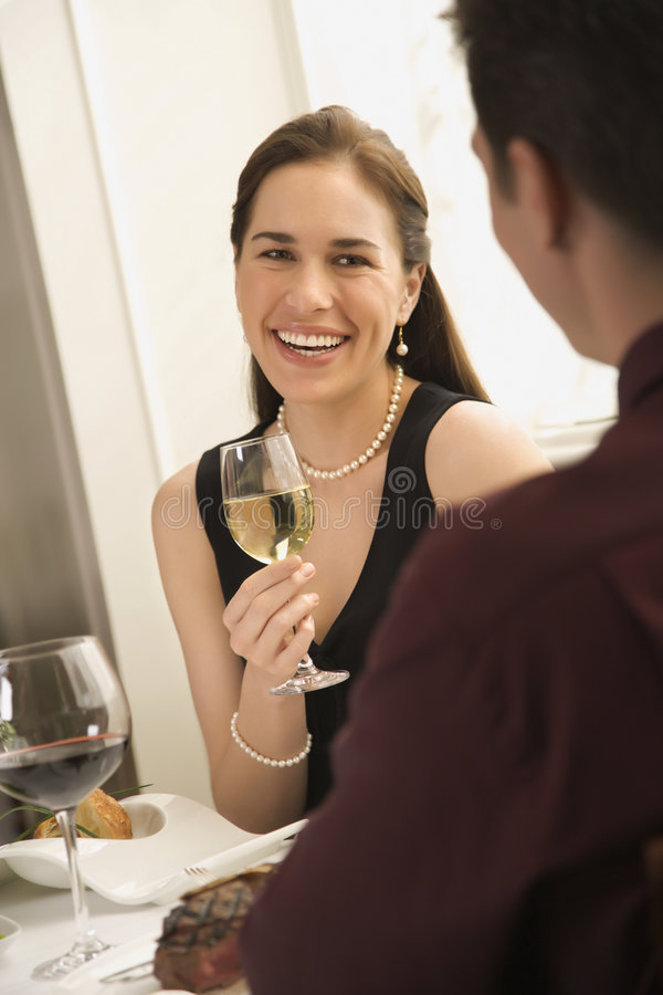 Couple drinking wine. Mid adult Caucasian couple smiling and drinking wine and dining stock image