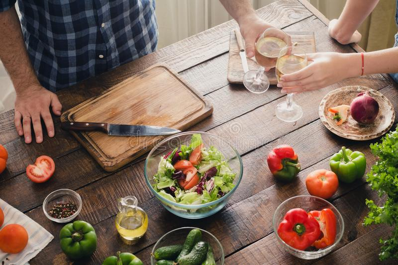 Couple drinking wine while cooking dinner in kitchen royalty free stock image