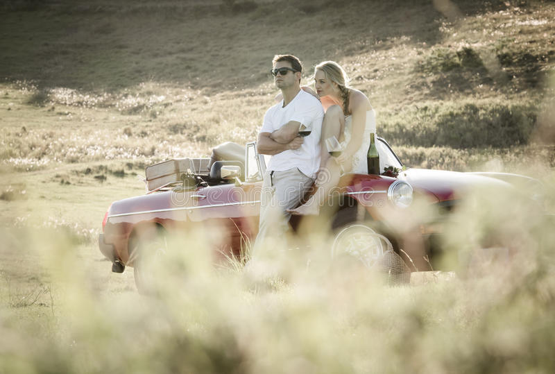Couple drinking wine in a grass field on a vintage sports car. Young couple drinking wine in a grass field on a vintage sports car royalty free stock image