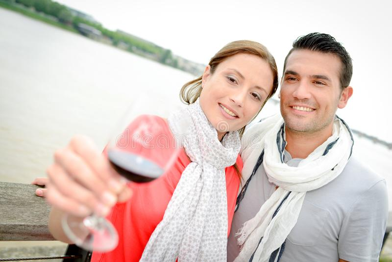 Couple drinking wine by river royalty free stock image