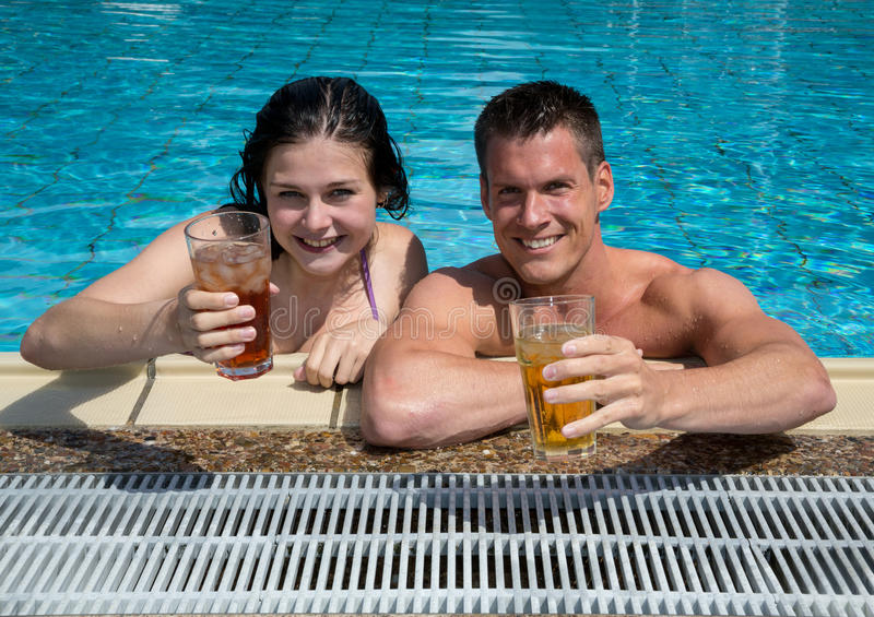 Couple with drinks in the sund at pool royalty free stock photo