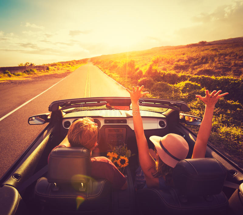 Couple Driving Convertable at Sunset stock photos