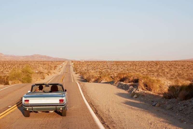 Couple driving convertible car on desert highway, back view stock images